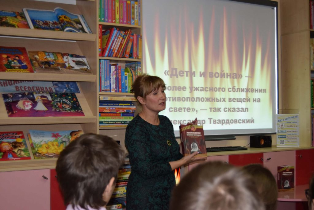 библиотекарь показывает книгу читателям