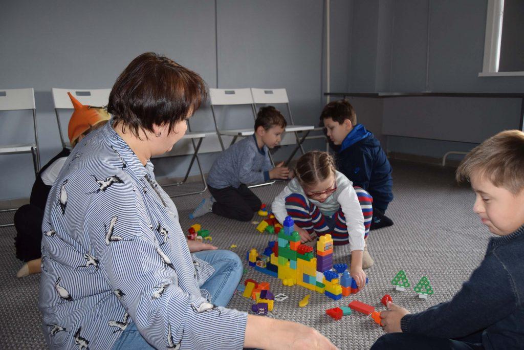 Ведущая и дети играют в конструктор